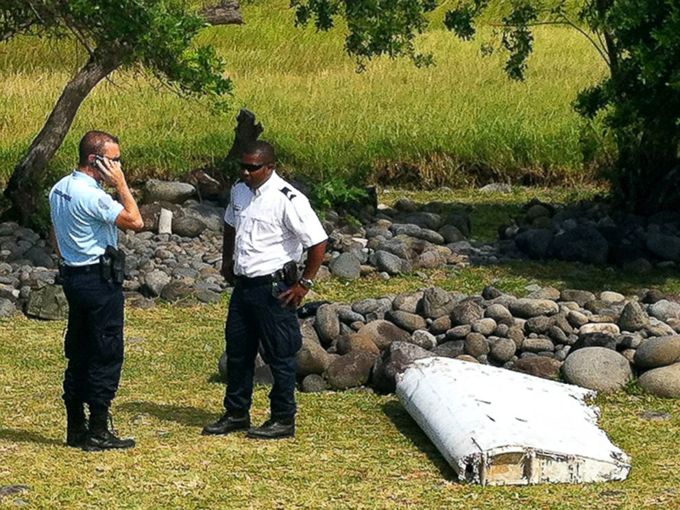 PHOTO: Policemen stand next to a piece of debris from an unidentified aircraft, July 29, 2015, found in the coastal area of Saint-Andre de la Reunion, in the east of the French Indian Ocean island of La Reunion