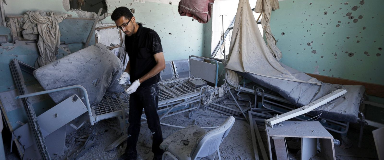 PHOTO: A Palestinian employee inspects the damage to a room at the Al-Aqsa Martyrs hospital in Deir al-Balah in the central Gaza Strip after the building was shelled by the Israeli army on July 21, 2014.