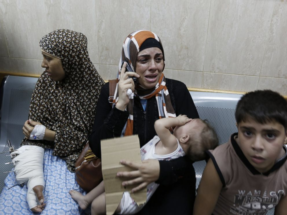 PHOTO: Palestinian patients sit in a hallway of the Al-Aqsa Martyrs hospital in Deir al-Balah in the Gaza Strip after the building was hit by an Israeli army shelling on July 21, 2014.