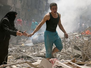PHOTO: People walk amid the rubble of destroyed buildings following an air strike on the rebel-held neighbourhood of al-Kalasa in the northern Syrian city of Aleppo, April 28, 2016.
