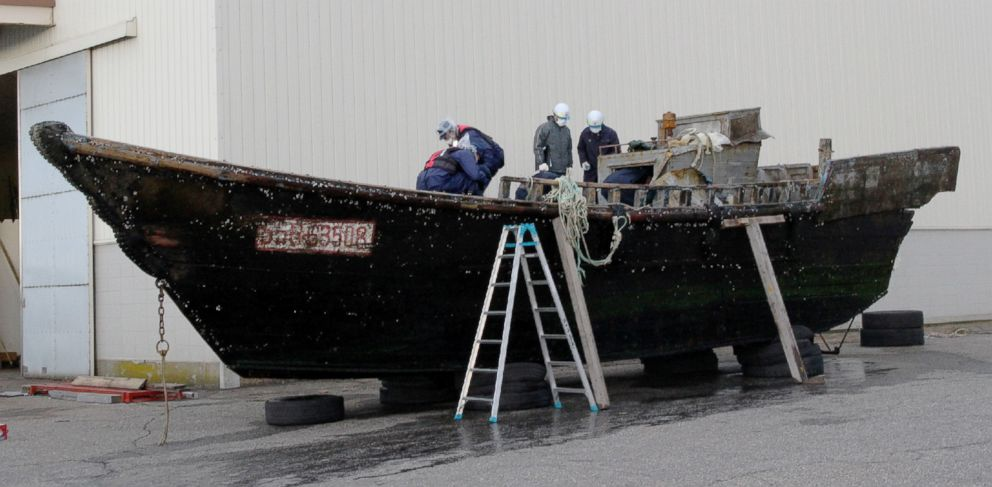 PHOTO: This picture taken on Nov. 24, 2015 shows coast guard officials investigating a wooden boat at the Fukui port in Sakai city in Fukui, Japan.