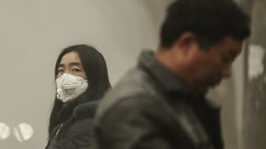 PHOTO: A woman wears a face mask next to traffic shrouded in heavy smog on Dec. 1, 2015 in Beijing, China.