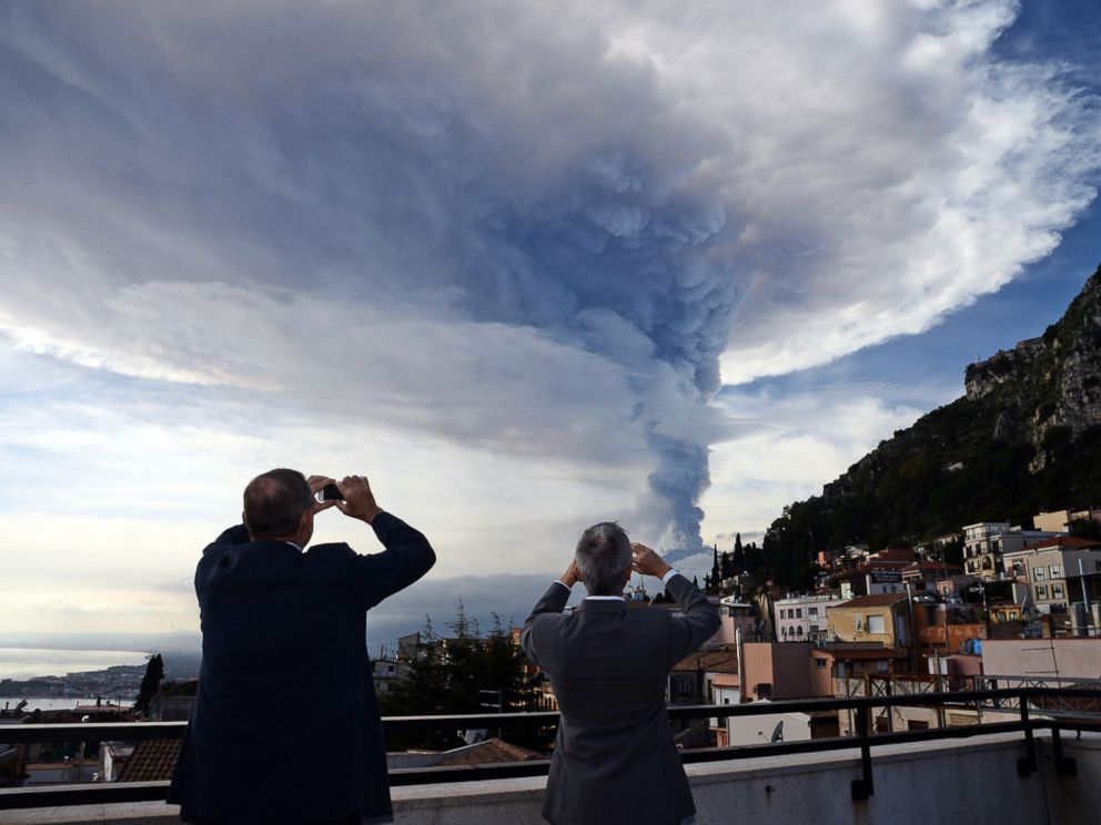 PHOTO: People take pictures of the smoke rising over the city of Taormina during an eruption of the Mount Etna, one of the most active volcanoes in the world, near Catania, Dec. 4, 2015.