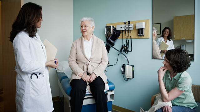 PHOTO: Mature female patient in exam room with doctor.