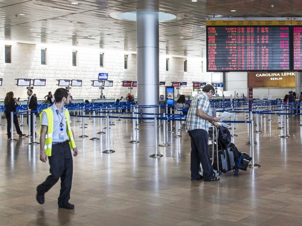 PHOTO: Israeli passengers walk near a departure time flight board displaying various cancellations at Ben Gurion International airport, near Tel Aviv, on July 23, 2014.