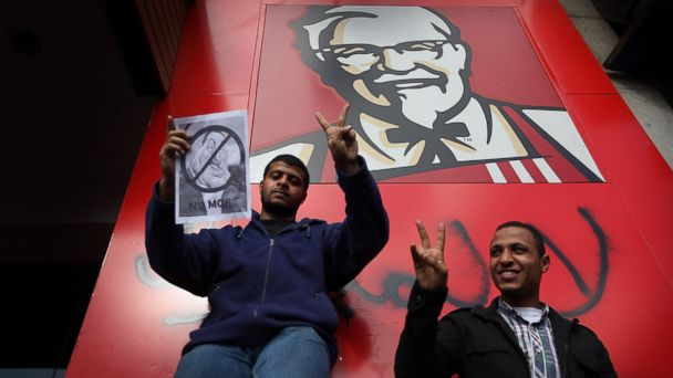 PHOTO: Protestors gesture as they stand next to a Kentucky Fried Chicken restaurant on January 31, 2011 in Cairo, Egypt.