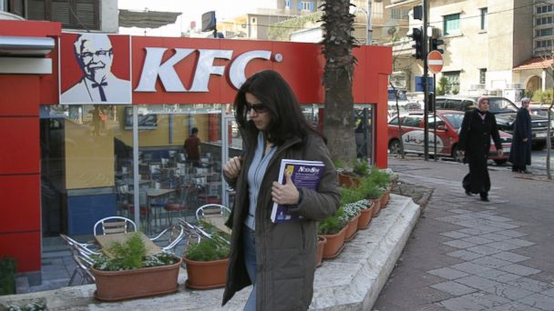 PHOTO: Syrian women walk past a newly opened Kentucky Fried Chicken (KFC) restaurant in Damascus on January 23, 2006.