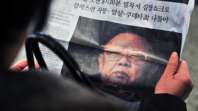PHOTO: A woman reads a copy of an extra edition newspaper reporting the death of Kim Jong Il.