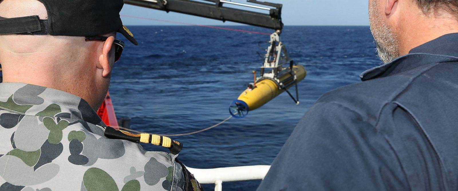 """PHOTO: In this handout image provided by the Australian Department of Defense, Commander James Lybrand and Chris """"Sharkie"""" Moore, watch the launching the Phoenix Autonomous Underwater Vehicle Artemis off the deck of ADV Ocean Shield on April 17, 2014."""