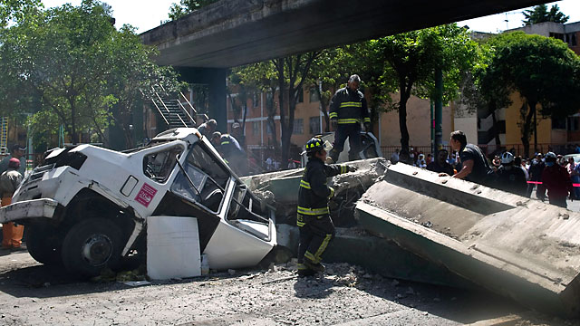 PHOTO: Firefighters work to remove a bus damaged by a bridge which collapsed following a strong quake that hit Mexico, March 20, 2012.