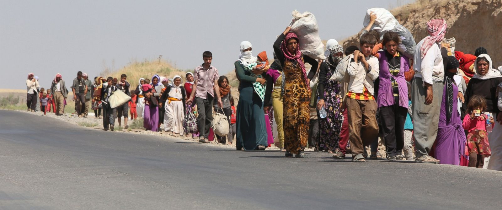 PHOTO: Displaced Iraqi families from the Yazidi community cross the Iraqi-Syrian border at the Fishkhabur crossing, in northern Iraq, on August 13, 2014.