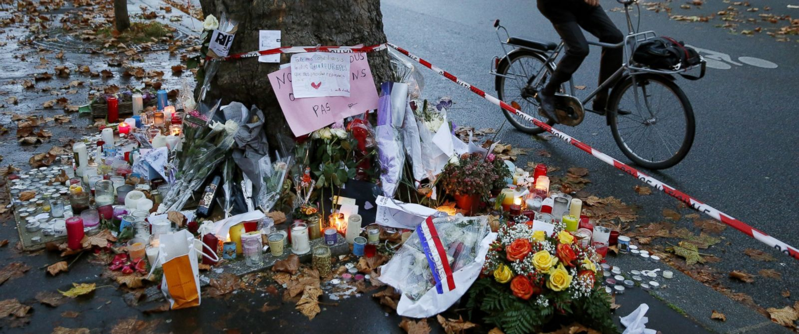 PHOTO: A cyclist pauses to look at candles and floral tributes to victims of the attacks at the Bataclan Theater in Paris on Nov. 17, 2015, where at least 82 people were killed.