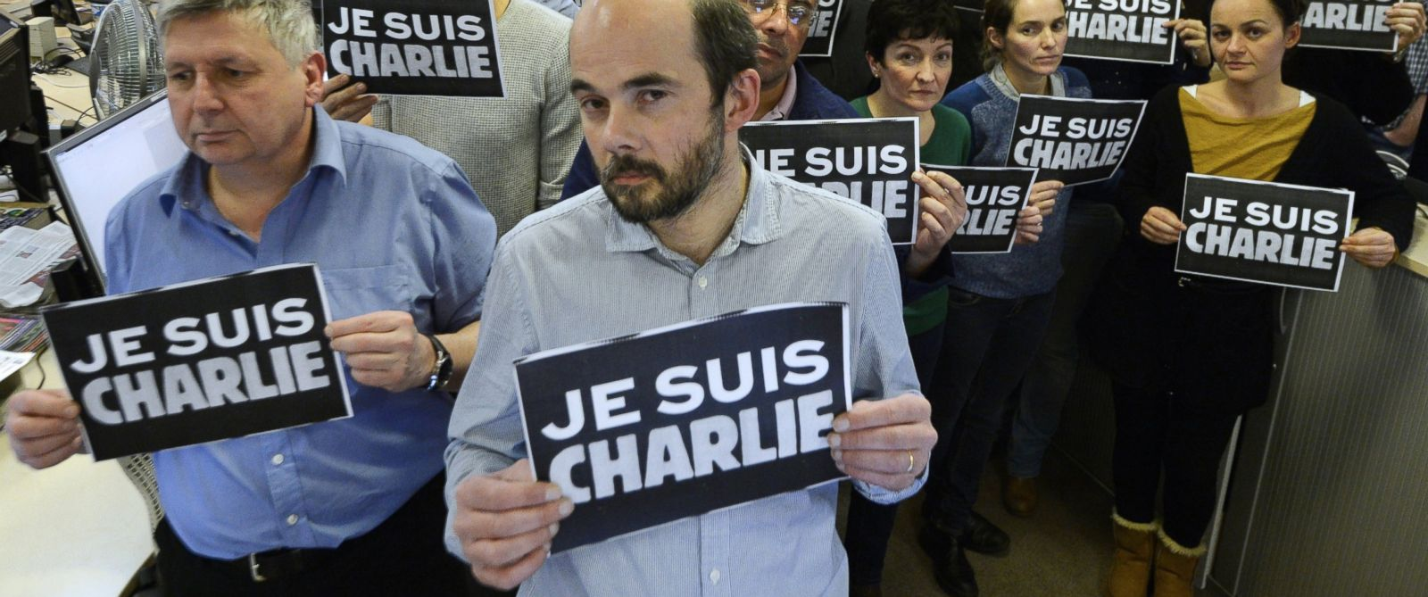 """PHOTO: Journalists hold placard reading """"I am Charlie"""" as they hold a minute of silence at the French news agency Agence France Presse, following the attack by gunmen in the offices of the French satirical weekly Charlie Hebdo, Paris, Jan. 7, 2015."""