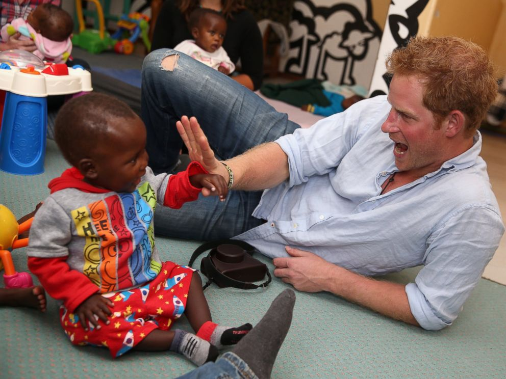 PHOTO: Prince Harry plays with two young children during a visit to the organisation supported by Sentebale, Touching Tiny Lives, on Dec. 8, 2014 in Mokhotlong, Lesotho.
