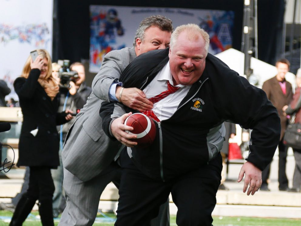 PHOTO: Mayor Rob Ford gets tackled by his Press-Secretary George Christopoulos during Grey Cup celebrations at the CFL Adrenaline Zone at Nathan Phillips Square, Nov. 20, 2012 in Toronto, Canada.