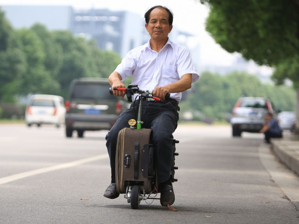 PHOTO: Chinese farmer He Liangcai spent ten years developing his motorized scooter suitcase and rides it regularly around Changsha, central Chinas Hunan province.