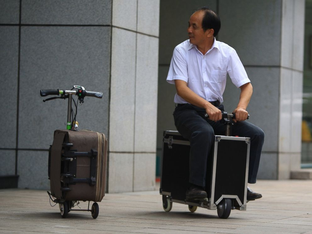PHOTO: Chinese farmer He Liangcai rides a motorized scooter suitcase that he invented on the street in Changsha, central Chinas Hunan province, May 28, 2014.