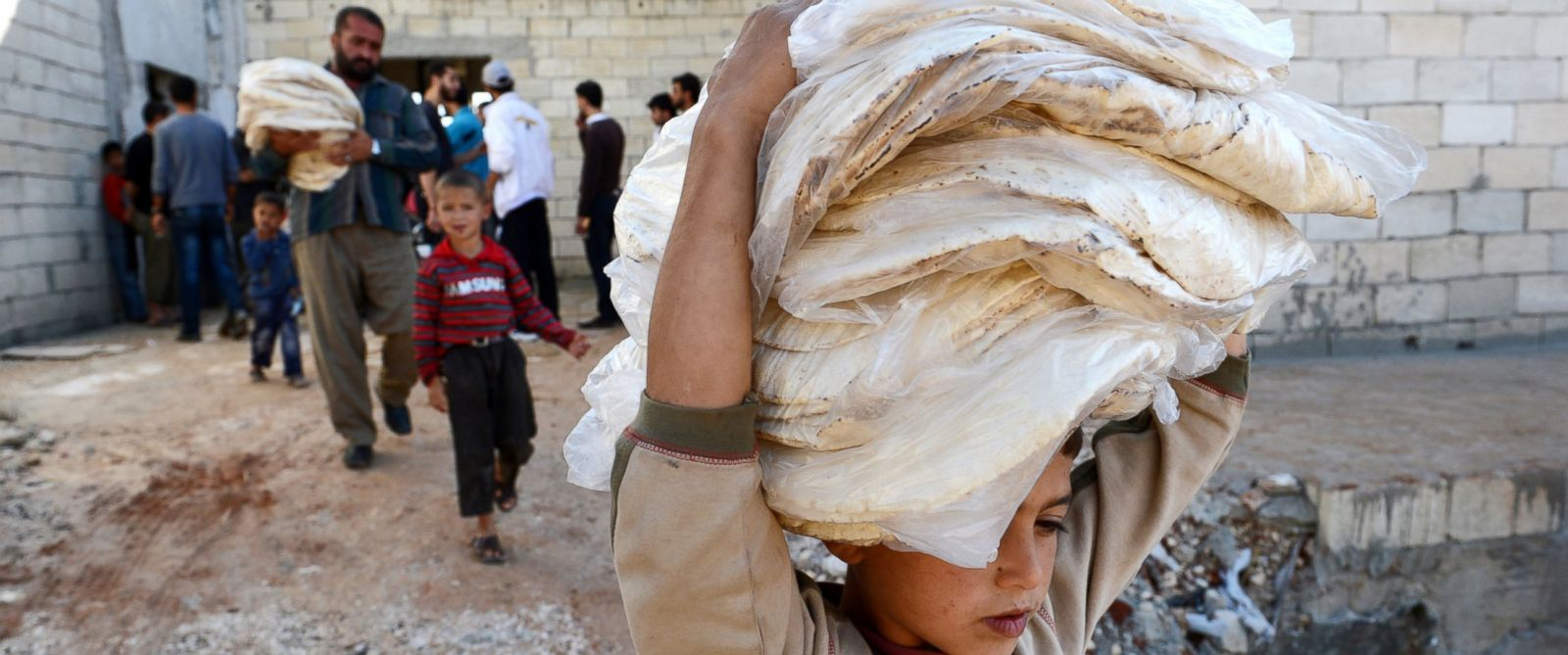 PHOTO: A Syrian boy carries bread in the northern Syrian town of Atareb in the Aleppo province in this file photo from Nov. 7, 2012.