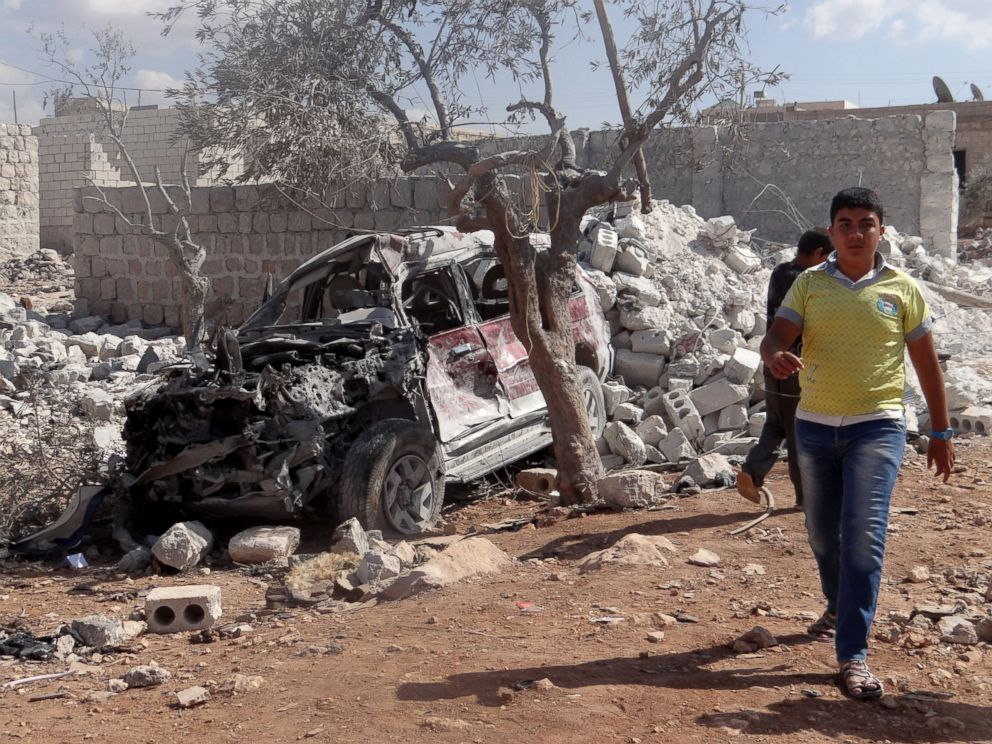 PHOTO: A Syrian youth walks past the wreckage of a vehicle following the U.S.-led coalition airstrikes against ISIS in a residential area in Idlib, Syria on Sept. 23, 2014.
