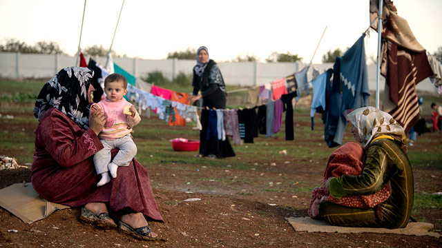 PHOTO: Mothers and their children sit among their washing in a refugee camp on the border between Syria and Turkey near the northern city of Azaz on Dec. 5, 2012.