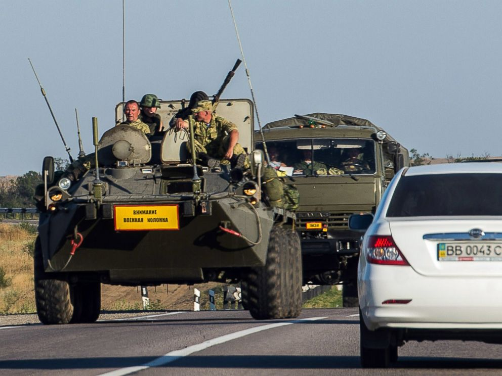 PHOTO: A Russian armored personnel carrier leads a column of military vehicles on a road near the town of Kamensk-Shakhtinsky in the Rostov region, some 30 km from the Russian-Ukrainian border, on August 15, 2014.