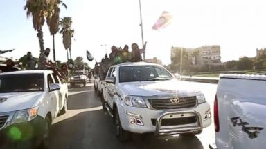 PHOTO: ISIS fighters parade through the streets of Raqqa in a propaganda video released online in July 2014.