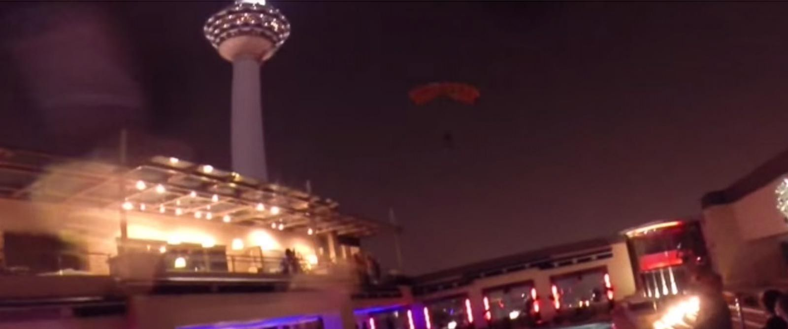 PHOTO: A base jumpers parachute can be seen between the Kuala Lumpur tower from where he jumped and the swimming pool where he landed shortly after in this screen grab from a video posted to YouTube, Oct. 4, 2014.