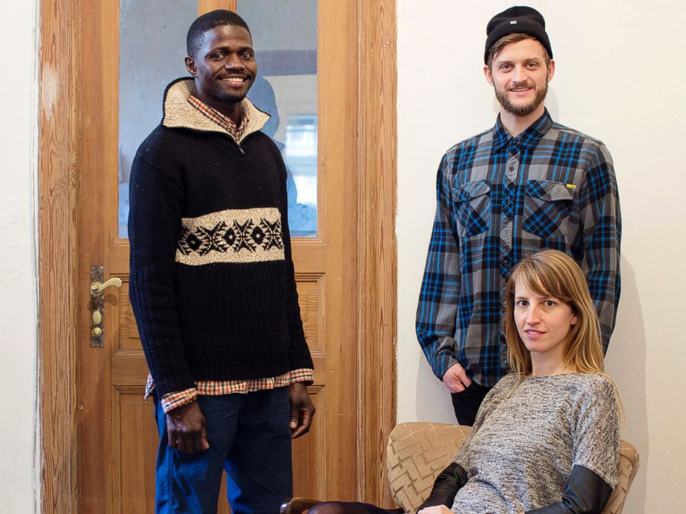 PHOTO: Refugees Welcome founders Mareike Geiling and Jonas Kakoschke pose with Bakary, a refugee from Mali that they hosted, in an undated handout photo.