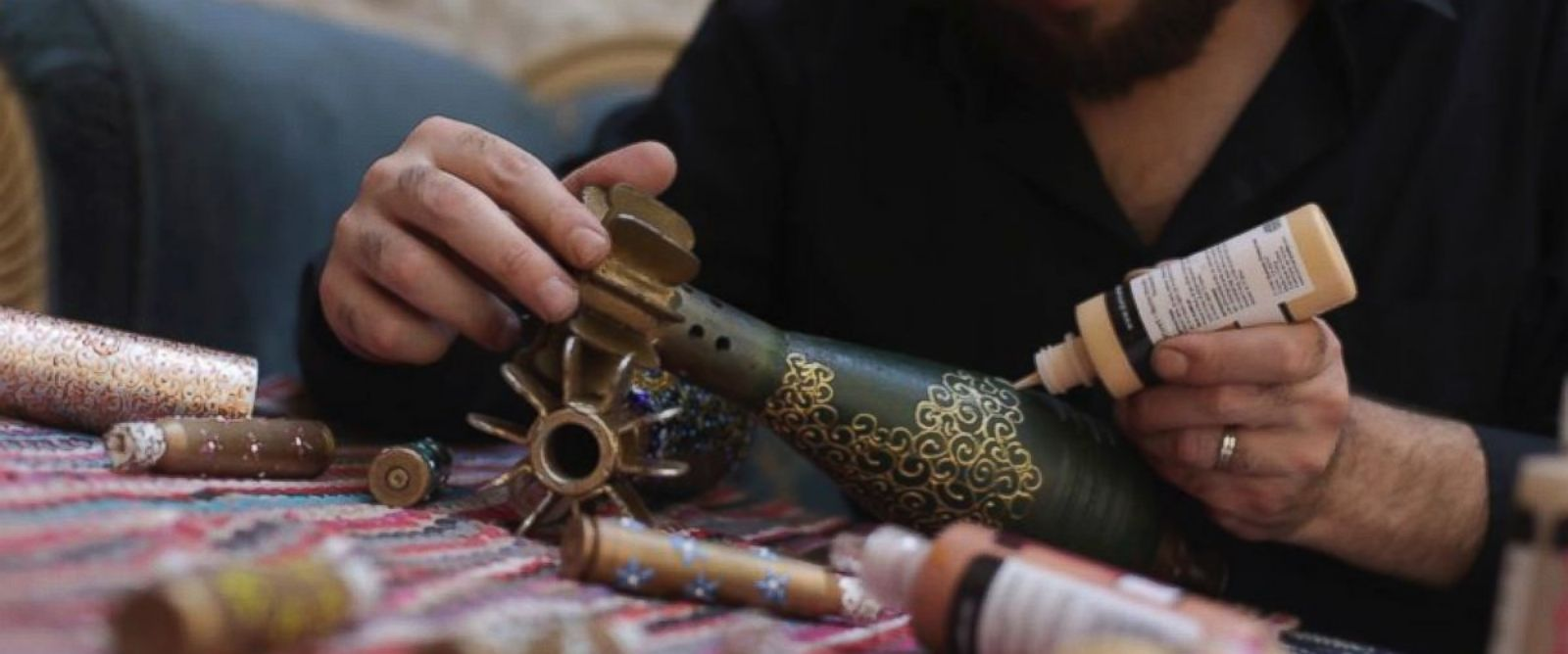 PHOTO: Douma-based artist Akram Abou al-Fouz at work, painting on mortar shells.