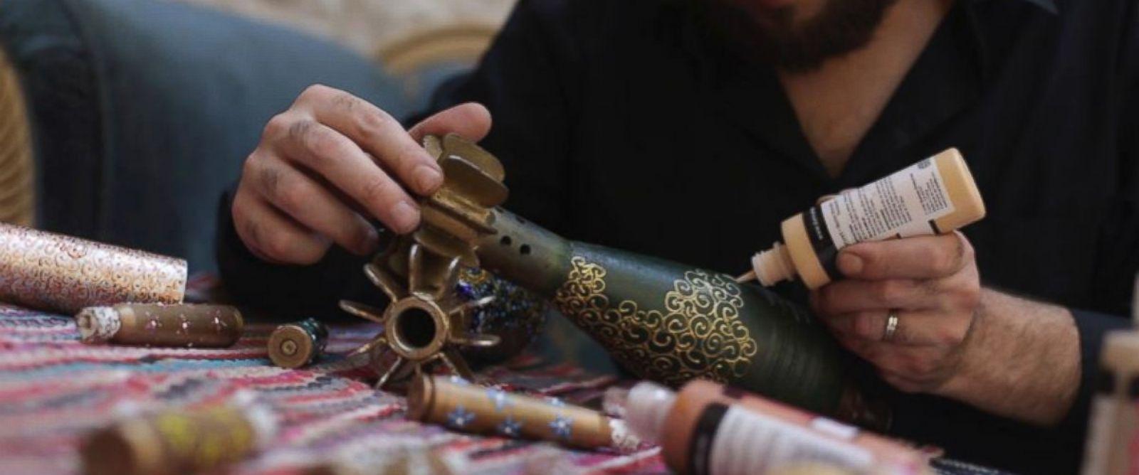 PHOTO: Douma-based artist Akram Abou al-Fouz at work, painting on mortar shells.