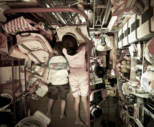 Children Do Homework While Their Parents Go About Daily Routine In Family Apartment The Urban Slums Of Hong Kong Benny Lam Soco Rex Usa