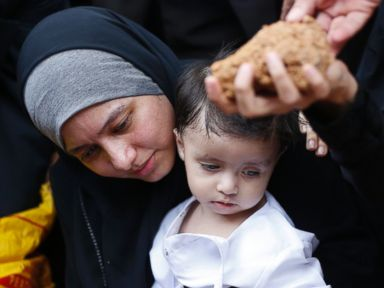 PHOTO: Asmaa Aljuned, holding her nine-month-old son Abderrahman, throws dirt into the grave of her husband, MH17 First Officer Ahmad Hakimi Hanapi, in Putrajaya August 22, 2014.