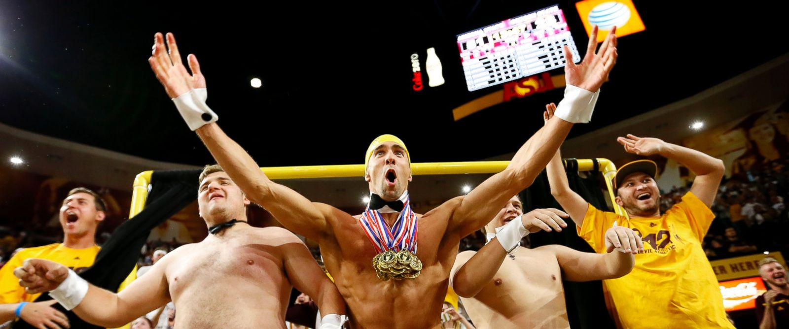 """PHOTO: Olympic swimmer Michael Phelps, center, performs behind the """"Curtain of Distraction"""" during an Oregon State free throw against Arizona State in the second half of an NCAA college basketball game, Jan. 28, 2016, in Tempe, Ariz."""
