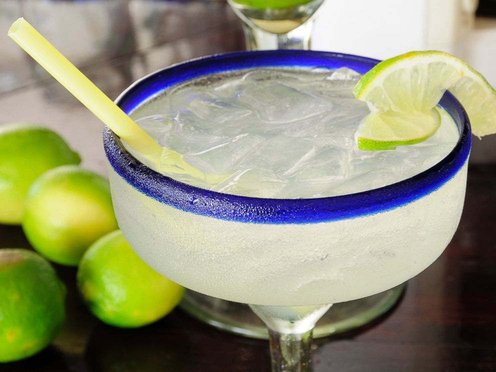 PHOTO: A frosted glass of a margarita cocktail served with ice and slice of lime with whole limes at side is pictured in this undated photo.