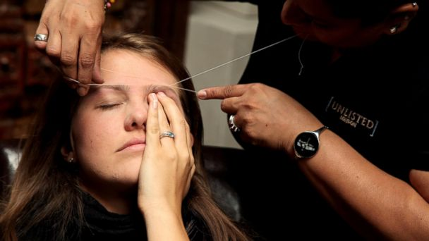 PHOTO: A woman has her eyebrows threaded at the Designer Couture Trunk Show hosted by Noelle Reno at The Collection in London, June 10, 2009.