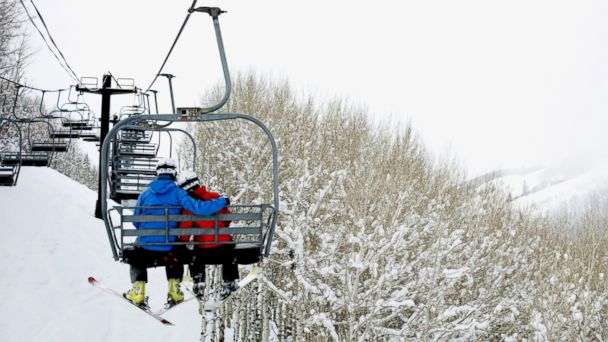 PHOTO: Skiers on a lift at a resort.