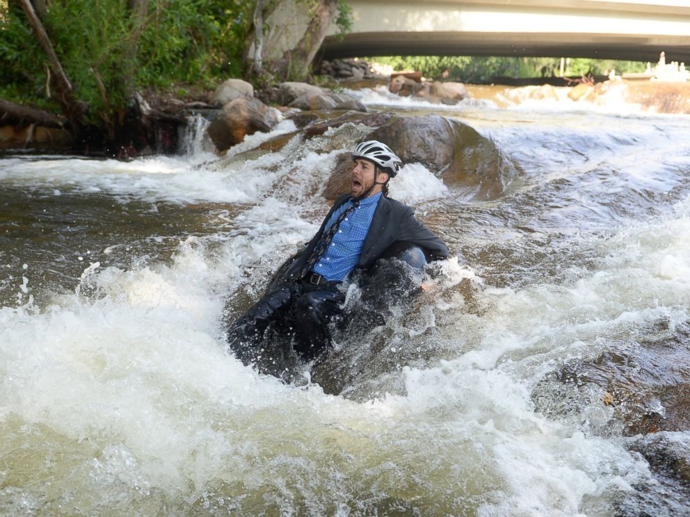 PHOTO: Quayle Hodek, dressed in a suit and tie, floats down Boulder Creek during Boulders Tube to Work Day, July 15, 2014.