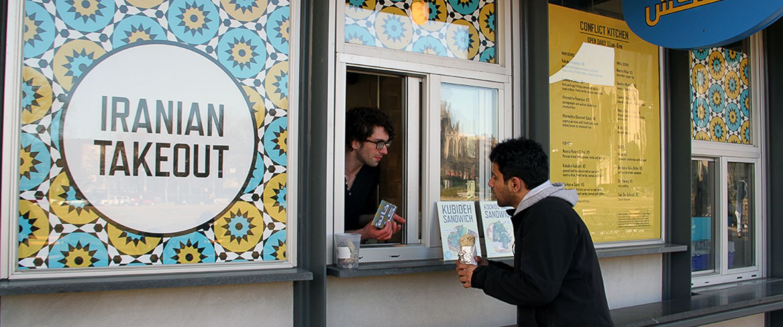 PHOTO: A customer at the takeout window of Conflict Kitchen.