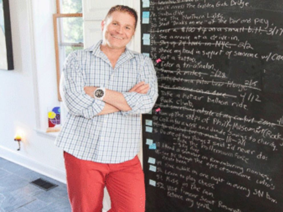 PHOTO: Dodd stands beside his floor-to-ceiling chalkboard where he crosses items off weekly.