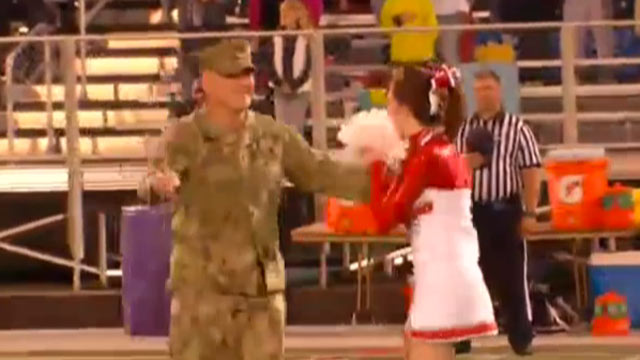 PHOTO: Petty Officer Dale Williams hid behind the Color Guard before surprising his daughter, Kendall at the Erwin High School's John G. Kerr Stadium in Asheville, NC.