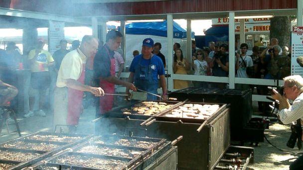PHOTO: Mitt Romney flips pork chops at the Iowa State Fair, Aug. 2011.