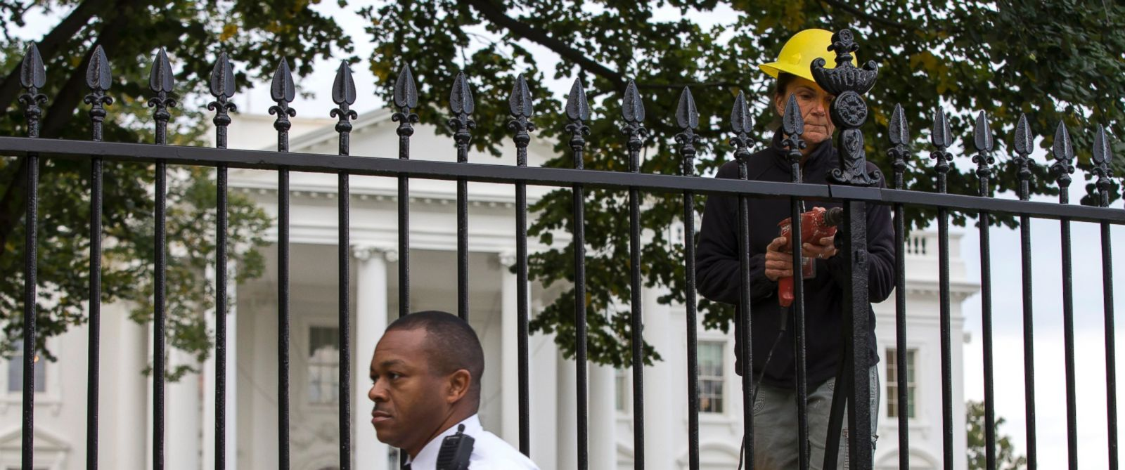 PHOTO: A Secret Service police officer walks outside the White House in Washington, Oct. 23, 2014, as a maintenance worker performs fence repairs as part of a previous fence restoration project.