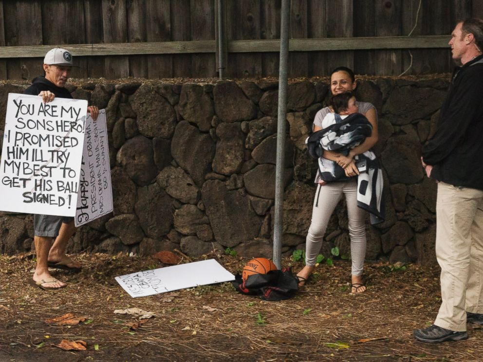 PHOTO: President Barack Obamas motorcade returns from golf as Cheyne Todani, left, holds a sign asking the president to sign a basketball for his son, Friday, Jan. 2, 2015, in Kailua, Hawaii.
