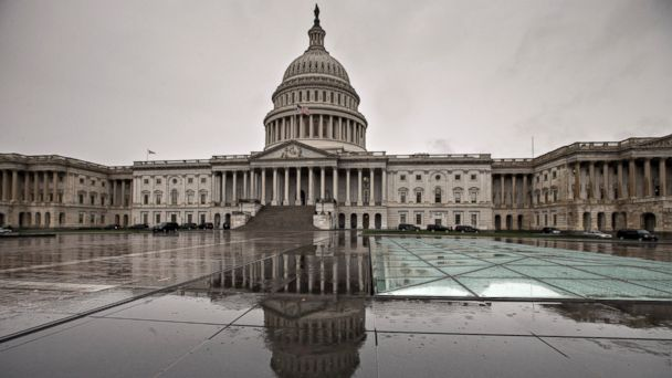 PHOTO: The U.S. Capitol is reflected during rain in Washington, Oct. 7, 2013.