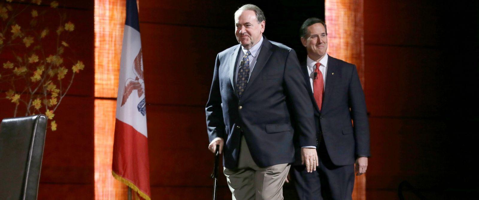 PHOTO: Republican presidential candidates former Arkansas Gov. Mike Huckabee and former Pennsylvania Sen. Rick Santorum, right, walk on the stage at the start of the Presidential Family Forum, Nov. 20, 2015, in Des Moines, Iowa.