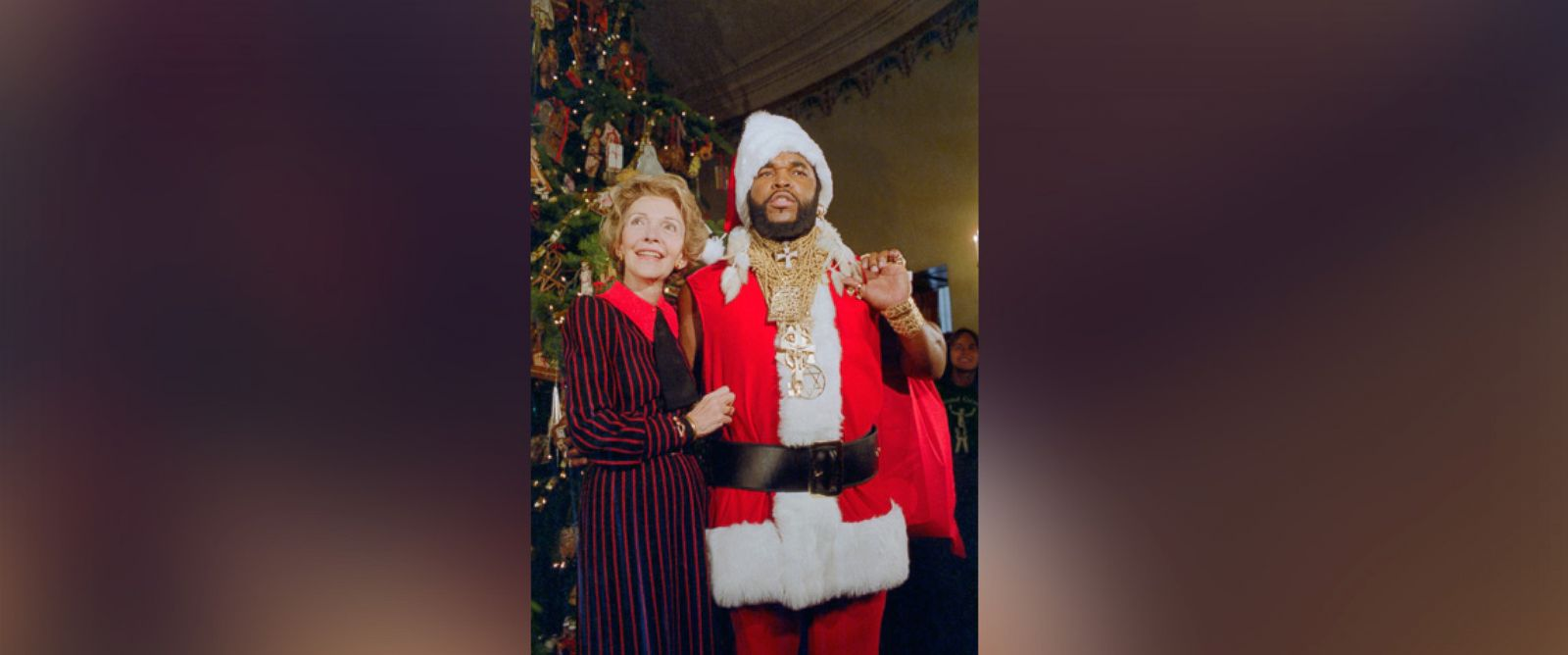 """PHOTO: Mr. T, of the television show the """"A-Team,"""" poses as Santa Claus to help First Lady Nancy Reagan unveil the White House Christmas decorations on Dec. 12, 1983 in Washington."""