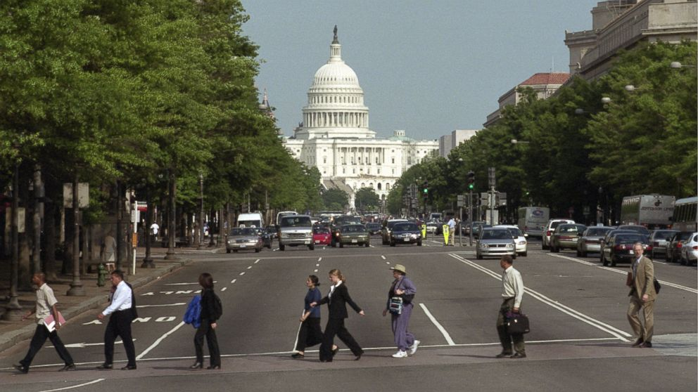 PHOTO: Pedestrians crossing the street in front of the Capitol building in Washington D.C.
