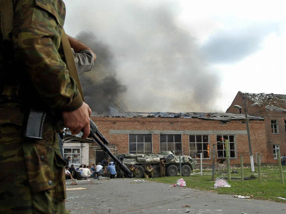 PHOTO: Soldiers and security forces are seen in front of the burning school during the rescue operation in Beslan, nortern Ossetia, Sept. 3, 2004.