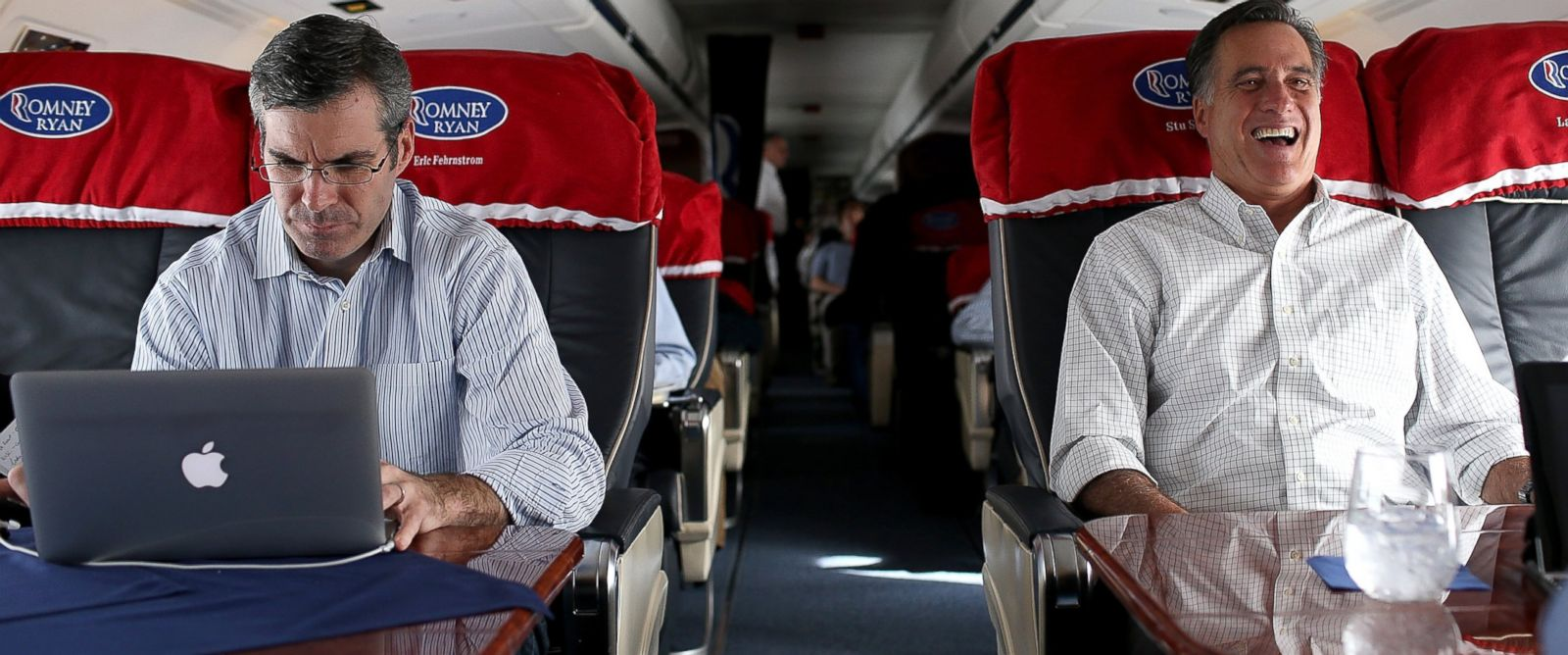 PHOTO: Then Republican presidential candidate Mitt Romney, right, laughs as his senior adviser and spokesman, Kevin Madden, works on his laptop on his campaign plane, Oct. 29, 2012, en route to Moline, Ill.