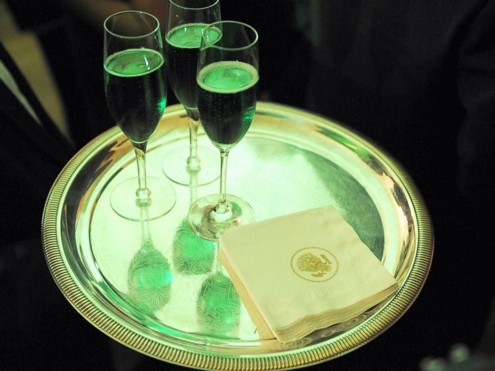 PHOTO: Glasses of green champagne are carried by a waiter during the annual St. Patricks Day reception in the East Room of the White House, March 17, 2009, in Washington.